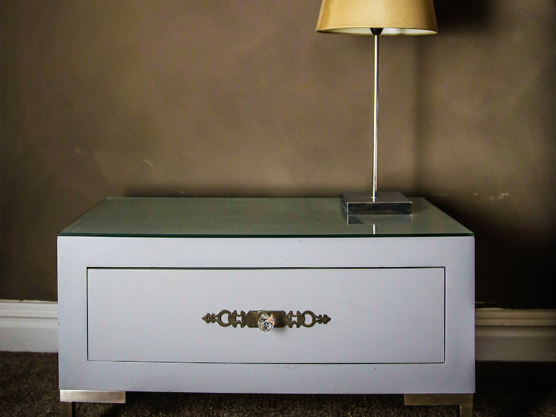 Contemporary styled bed side table with crystal knob and extrusion plate on stainless steel legs and glass counter top.